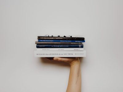 Hand holding up books against a white wall.