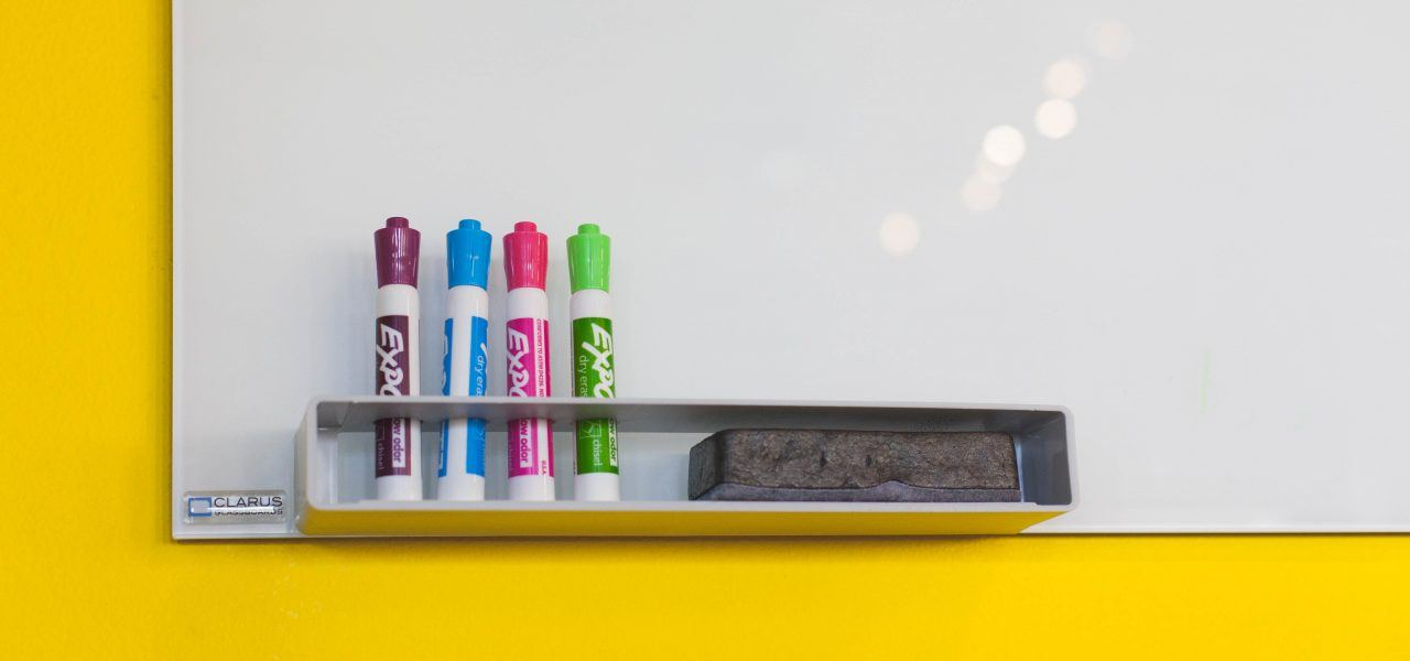 Corner of whiteboard with coloured pens and cleaner.