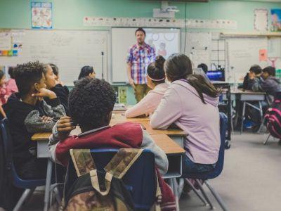 Teacher standing at front teaching class
