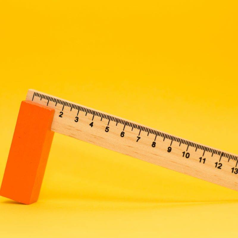 A wooden ruler against yellow background