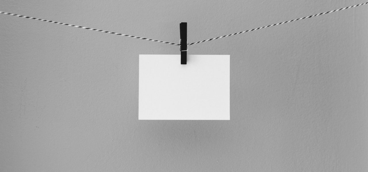 White card pegged onto string with black peg on grey background.